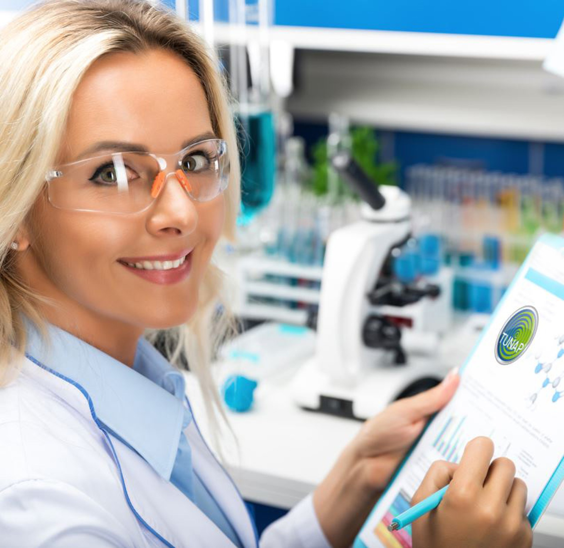 Smiling laboratory chemist wearing glasses and in the background a microscope and test tubes